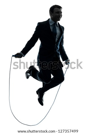 one caucasian businessman exercising jumping rope in silhouette studio isolated on white background - stock photo