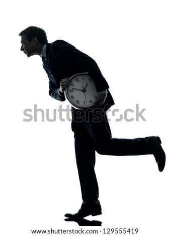 one caucasian businessman holding clock robbing time  in silhouette studio isolated on white background - stock photo