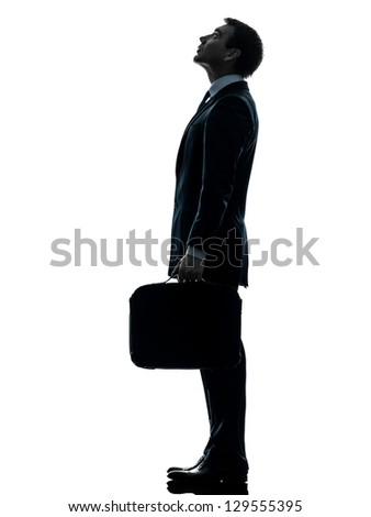 one caucasian businessman  standing looking up profile in silhouette studio isolated on white background