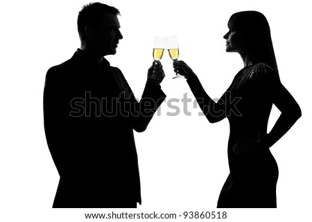 one caucasian couple man and woman drinking champagne toasting partying in studio silhouette isolated on white background - stock photo