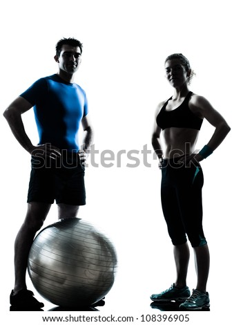 one caucasian couple man woman personal trainer coach exercising fitness ball silhouette studio isolated on white background - stock photo