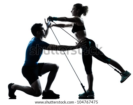 one caucasian couple man woman personal trainer coach exercising gymstick silhouette studio isolated on white background - stock photo