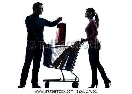 one caucasian couple woman man with shopping cart  and gifts in silhouette studio isolated on white background - stock photo