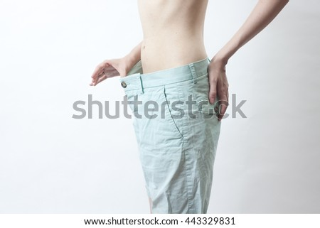 one Caucasian girl in green shorts after weight loss shows that they are great showing off how thin on white background