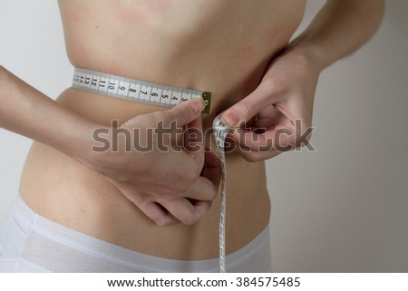 one caucasian girl in white underwear measuring the waist and hips on a white background