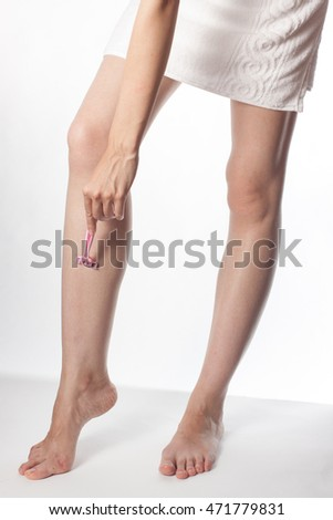 one Caucasian girl shaves legs women's refillable razor with shaving cream on a white background