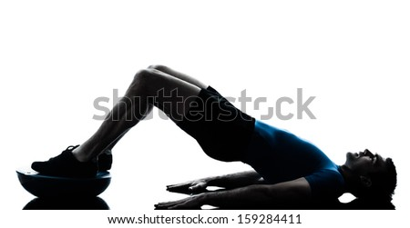 one caucasian man exercising bosu workout fitness in silhouette studio  isolated on white background - stock photo