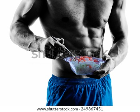 one caucasian man exercising fitness exercises eating salad  in studio silhouette isolated on white background - stock photo