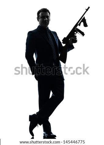one caucasian man holding thompson machine gun  in silhouette on white background - stock photo