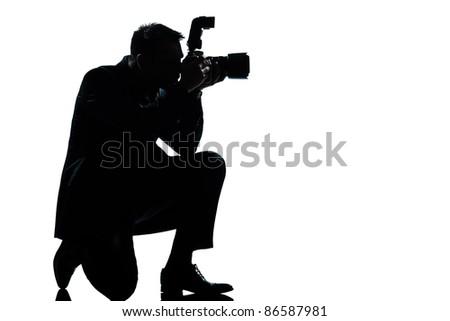 one caucasian man kneeling photographer full length silhouette in studio isolated on white background - stock photo