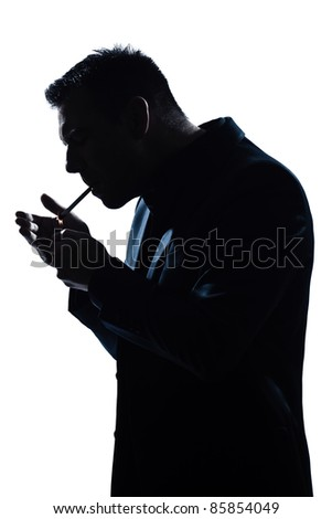 one caucasian man portrait smoking lighting cigarette silhouette in studio isolated white background - stock photo