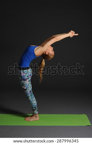 One caucasian woman exercising yoga on grey studio bacground. - stock photo