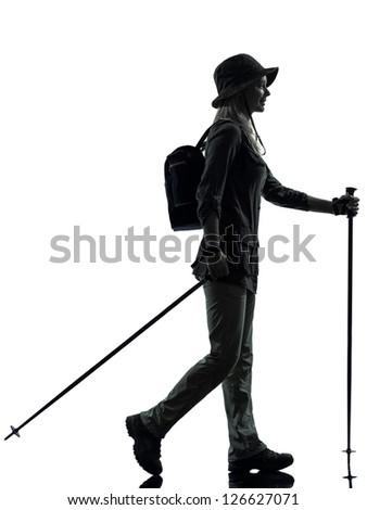 one caucasian woman trekker trekking walking in silhouette studio isolated on white background - stock photo