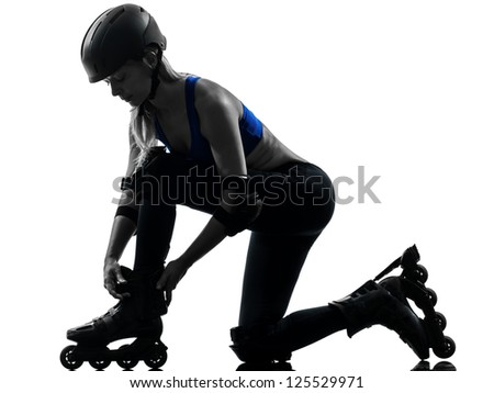 one caucasian woman tying roller skates  silhouette studio isolated on white background - stock photo