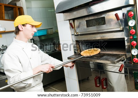 One chef baker in white uniform baking a pizza bread in oven at commercial kitchen
