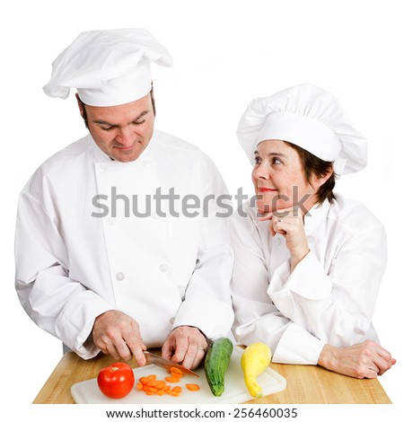 One chef observes another's prep work, chopping vegetables.  Isolated on white.