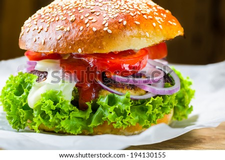one chicken burger with lettuce tomato ketchup mayonnaise and red onion - stock photo