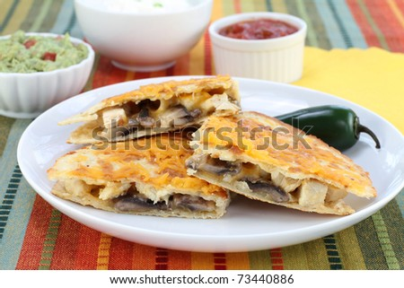 One chicken, mushroom and cheese Quesadilla on a plate with complimentary sauces to the side. - stock photo