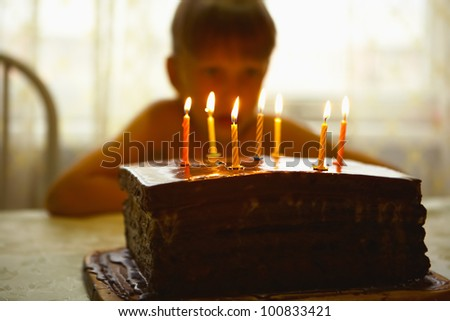 One child sits at a table and looks at a cake with candles. - stock photo