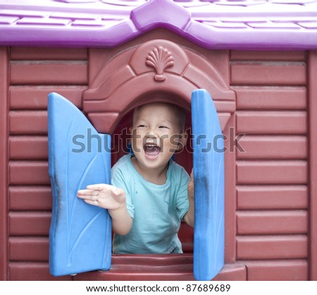 One chinese baby boy head out of the plastic window in the playground