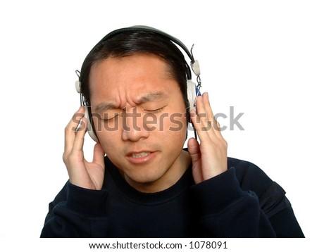 one chinese man enjoying  listening to music through his headphones.Isloated - stock photo