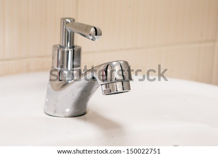 One chrome faucet in washbowl in bath room and white pile - stock photo