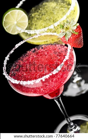 One Classic and a Strawberry Margarita in front of a black background with fresh garnish - stock photo