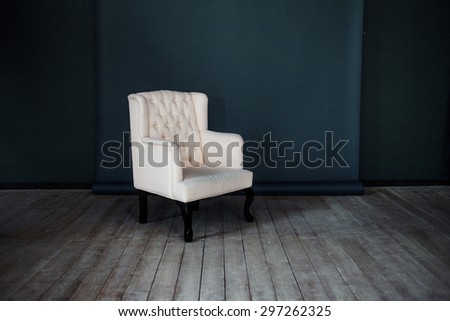 One classic armchair against a dark blue wall and floor. Copy space - stock photo