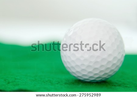 one clean new white golf ball on green artificial turf. Shallow definition of field with focus on the ball. The ball is on the right side of the image so there is room for your copy.  - stock photo