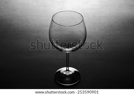 One clear empty wine glass standing on dark grey gradient textured background - stock photo