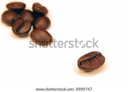 One coffee bean seperated from the a group of them on white.