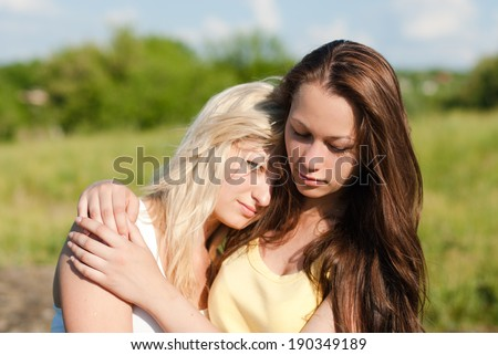 one comforts and expressing feelings of compassion for another: Two teenage girls,  beautiful young women girl friends having difficult times on the summer outdoors background closeup portrait - stock photo
