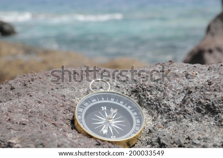 One Compass on the Rocks near the Atlantic Ocean - stock photo