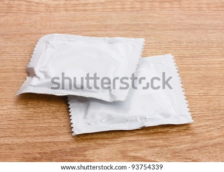 One condom on wooden background - stock photo