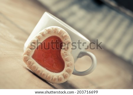one cookie in form of heart with words I Love You against cup on wood - stock photo