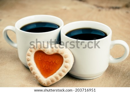 one cookie in form of heart with words I Love You and cup of coffee on wood - stock photo