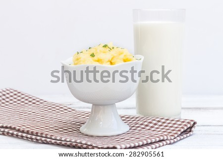 One cup of mashed potatoes and a glass of milk. - stock photo