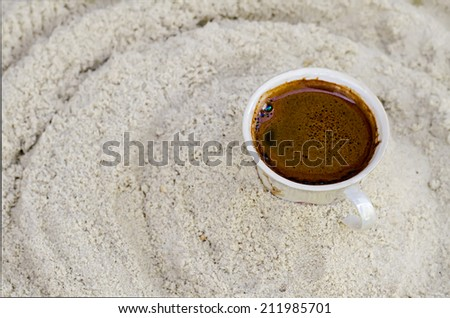 one cup with coffee costs on sand