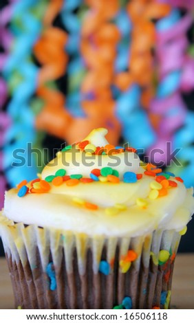 One cupcake with sprinkles and ribbons hanging in the background.  Used a shallow depth of field and selective focus on the middle part of cupcake and sprinkles.