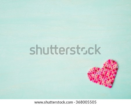 One Cute, pink and red Valentines Day Bead Craft Heart in corner on rustic textured cyan painted wood board background with room or space for copy, text, your words.  Horizontal looking down view