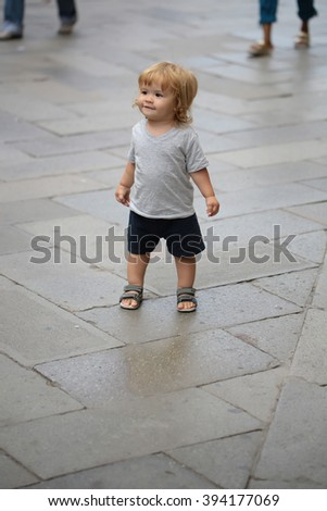 One cute smilig small chuld boy with blonde hair standing outdoor on street road looking away in stylish urban cloth, vertical picture - stock photo