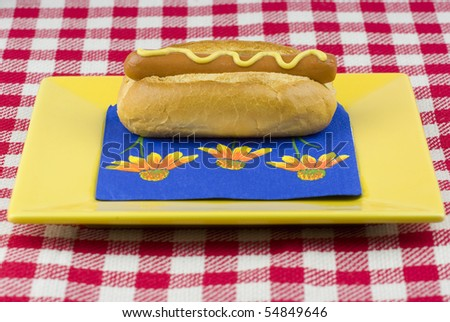 One delicious hot dog on a yellow plate. - stock photo
