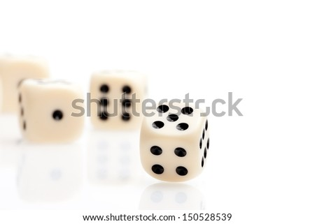 one dice in front of some dice unfocused on white table with space for text - stock photo