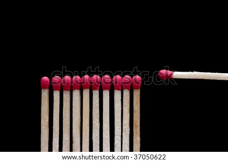 One different wooden match on black - stock photo