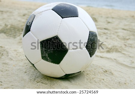 one dirty soccer ball sitting on the beach