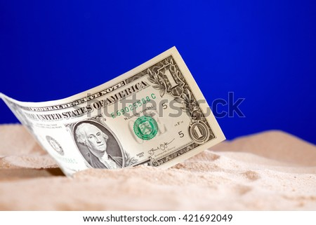 One dollar bank note on sand against blue background - stock photo