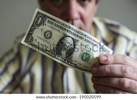 One dollar bill in the men's hand. - stock photo