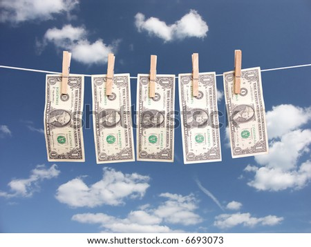 One dollar bills hanging on laundry line attached with wooden clips over blue sky - stock photo