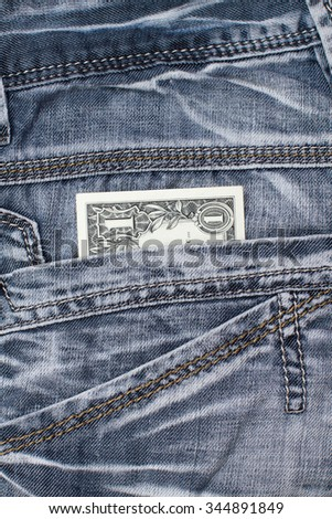 one dollar cash in jeans pocket close up