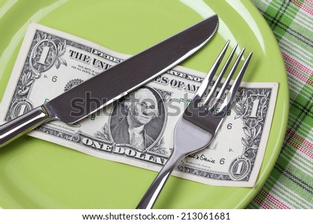 One Dollar Diet. One dollar on a plate with a knife and fork.